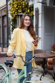 Смайлик женщина, держащая смартфон и велосипед в городе