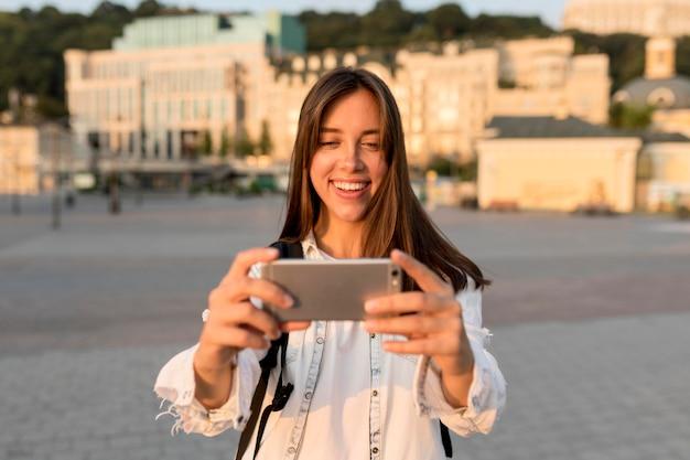 Смайлик женщина, держащая смартфон во время путешествия