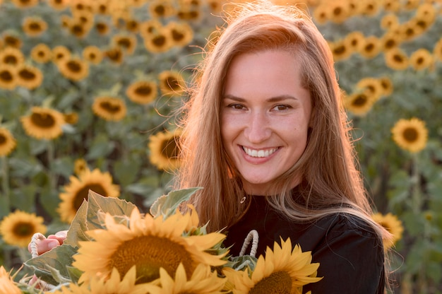 Smiley woman holding sunflowers