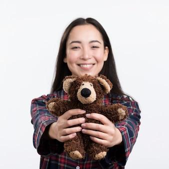 Smiley woman holding teddy bear