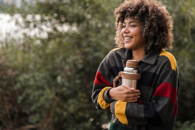Smiley woman holding thermos while camping outdoors with copy space