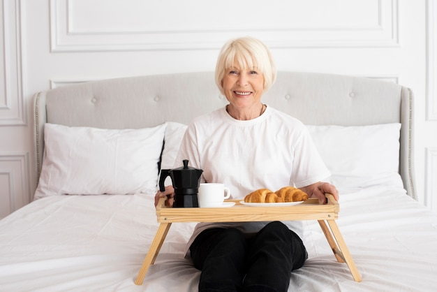 Smiley woman holding a tray in the bedroom