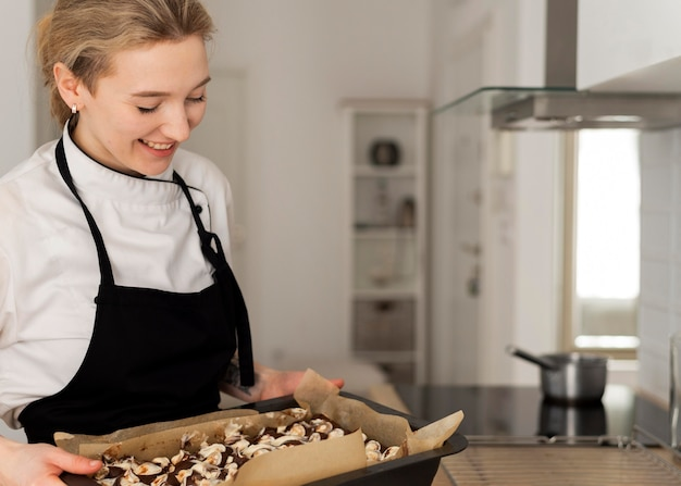 Smiley woman holding tray with dessert
