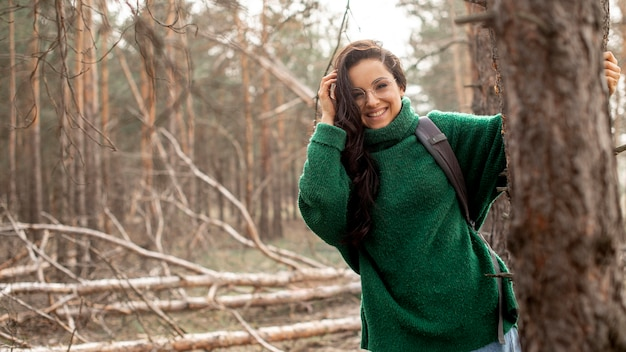 Smiley woman holding on tree