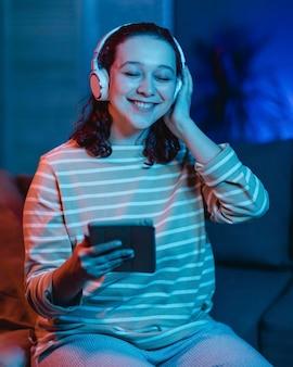 Donna sorridente a casa utilizzando cuffie e tablet