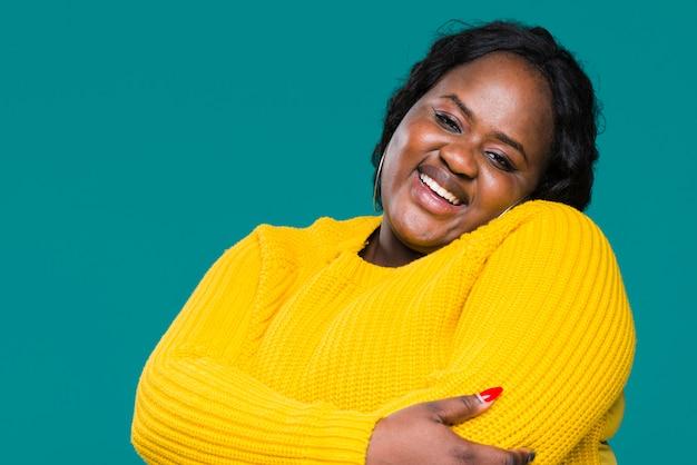 Smiley woman hugging herself