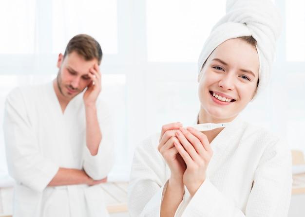 Улыбающаяся женщина в халате держит халат с обеспокоенным мужчиной