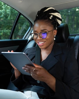 Смайлик женщина на заднем сиденье своей машины, глядя на планшет