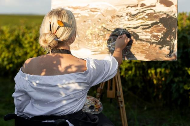 自然の絵で外の車椅子のスマイリー女性
