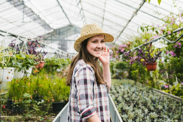 Smiley woman inside greenhouse