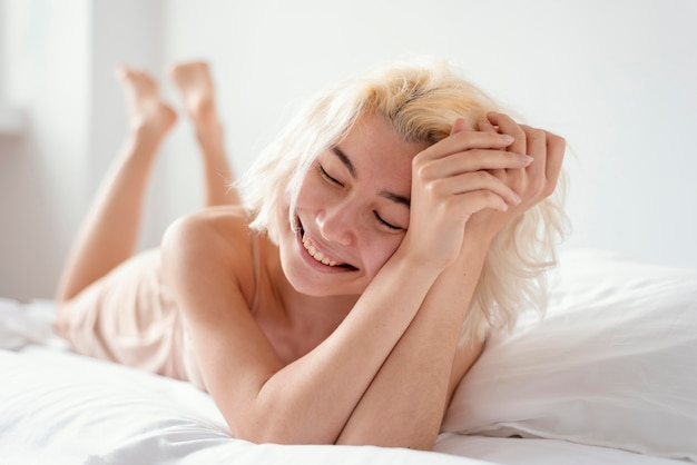 ベッドに横たわっているスマイリー女性フルショット