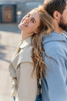 Smiley woman leaning against a man while outdoors