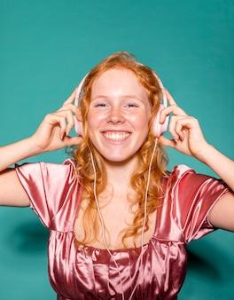 ヘッドフォンで音楽を聴いているスマイリー女性