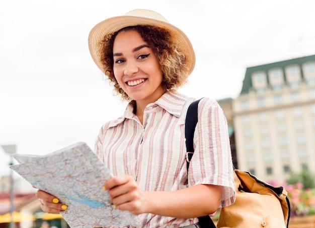 Смайлик женщина смотрит на свою карту для нового пункта назначения