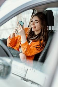 Смайлик женщина смотрит на свой телефон