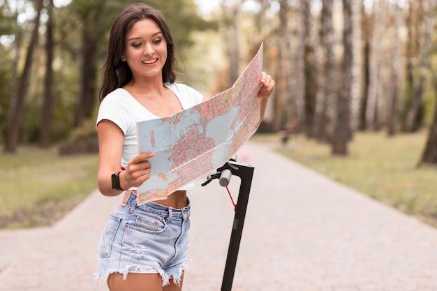 電動スクーターの横にある地図を見ているスマイリー女性