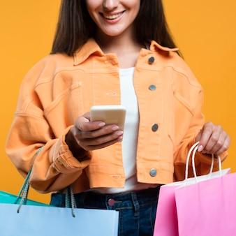 Donna sorridente guardando smartphone e tenendo un sacco di borse della spesa