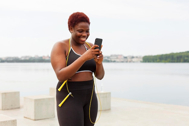 Donna sorridente guardando smartphone durante l'allenamento all'aperto