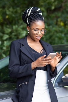 Smiley woman looking at smartphone while leaning against her car