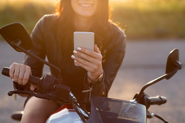 Smiley woman looking at smartphone while sitting on her motorcycle