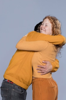 Smiley woman and man hugging
