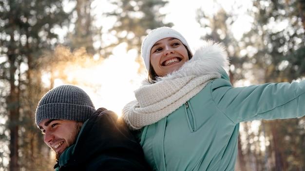 Donna e uomo di smiley insieme all'aperto in inverno