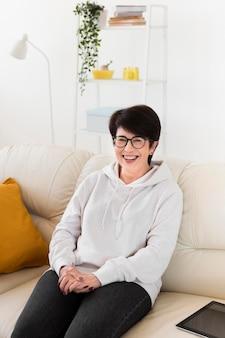 タブレットを自宅でソファの上のスマイリー女性