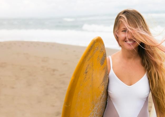 Смайлик женщина на пляже, держа доску для серфинга