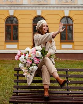 야외에서 봄에 꽃의 꽃다발을 들고 벤치에 웃는 여자