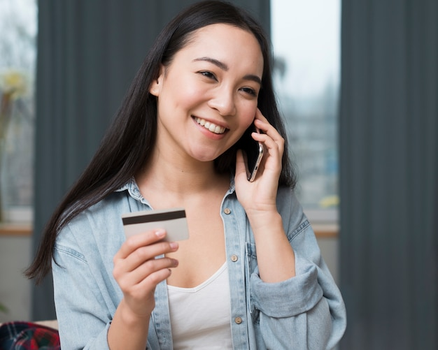 Smiley woman ordering online from her smartphone