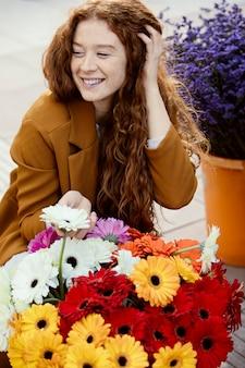 꽃의 부케와 함께 봄에 야외에서 웃는 여자