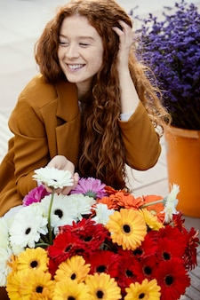 Smiley woman outdoors in spring with bouquet of flowers
