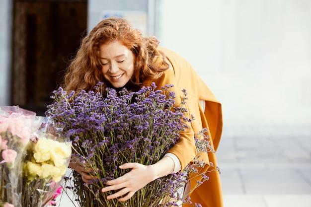 봄 꽃의 부케와 함께 야외에서 웃는 여자
