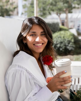 Smiley woman outdoors with coffee cup and flowers