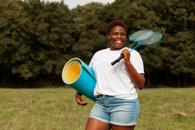 Donna sorridente all'aperto con racchette e materassino yoga