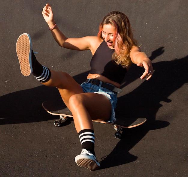スケートボードで屋外のスマイリー女性