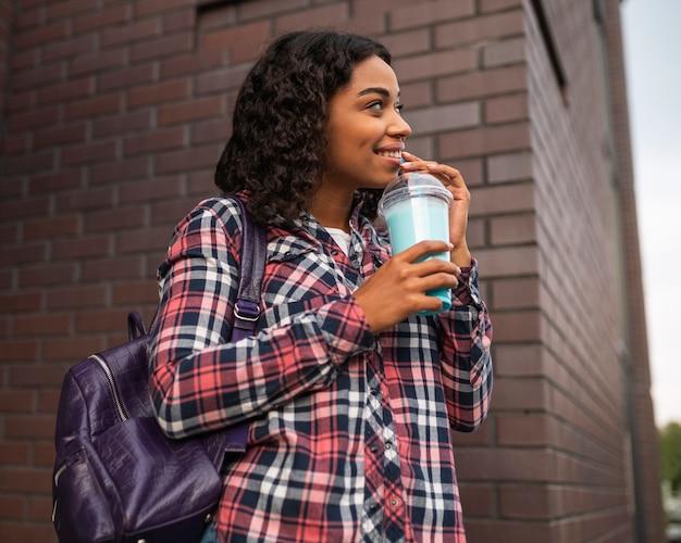 Смайлик женщина снаружи с молочным коктейлем