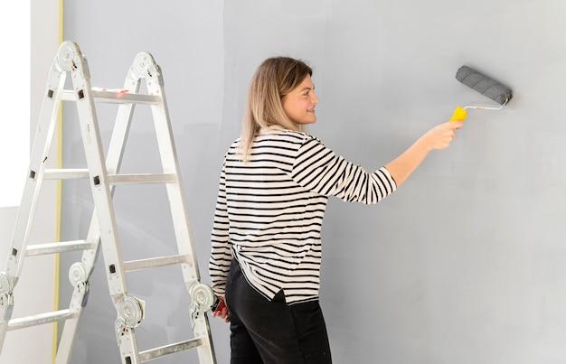 Smiley woman painting wall medium shot