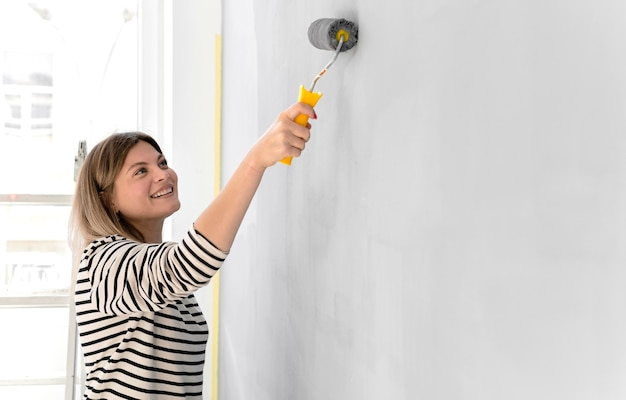 Smiley woman painting wall