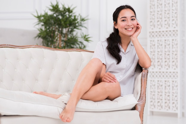 Smiley woman in pijama on couch