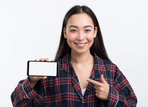Smiley woman in pijama pointing at phone