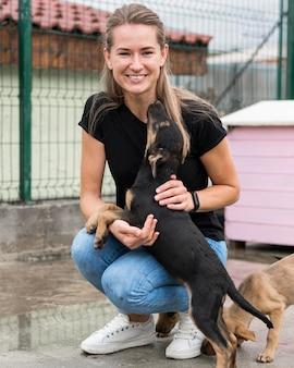 養子縁組センターで救助犬と遊ぶスマイリー女性