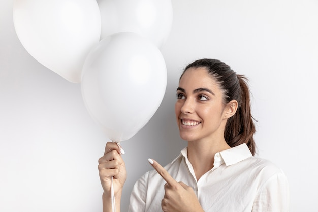 Smiley woman pointing at hand held balloons