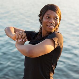 Смайлик женщина позирует после тренировки на берегу озера