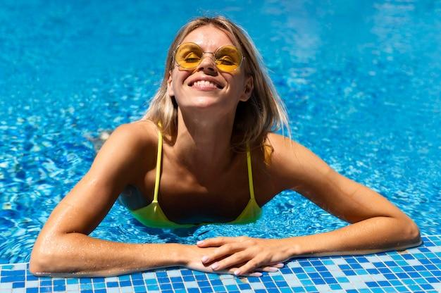 スマイリー女性がプールでポーズ
