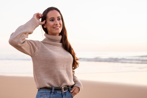 Smiley woman posing by the beach at sunset