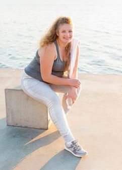 運動した後、湖のほとりでポーズをとるスマイリー女性