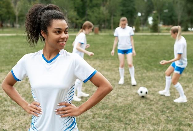 Donna sorridente in posa sul campo di calcio