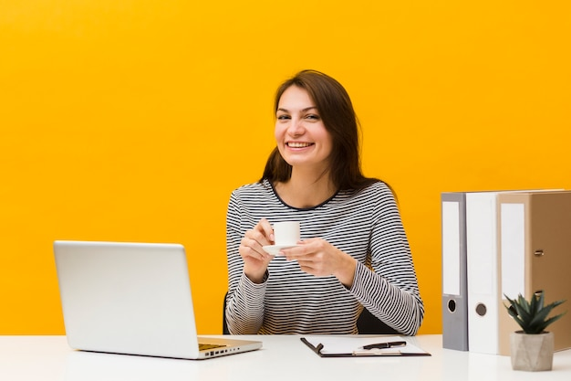 Smiley woman posing at her desk while holding cup of coffee