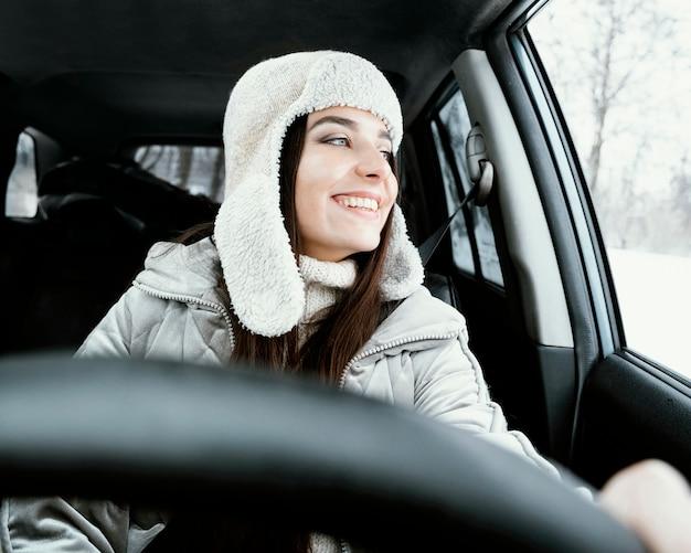도로 여행을하는 동안 차에서 포즈 웃는 여자